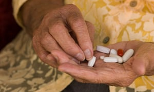 Older person's hand sorting through a handful of medications
