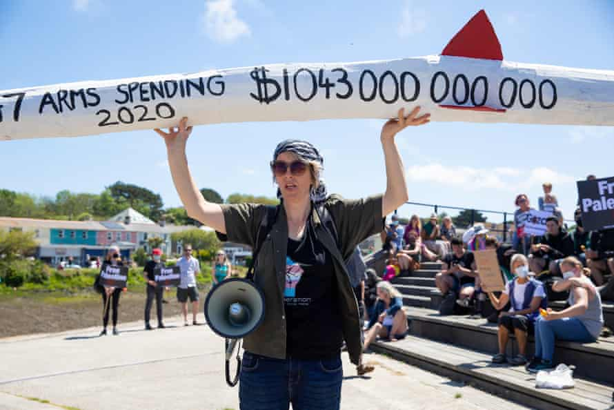 A civil rights protester showcasing the amount of money G7 countries spent on arms in 2020