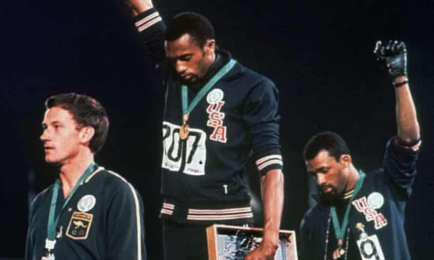Tommie Smith, center, and John Carlos (right) during the medal ceremony at the 1968 Olympics