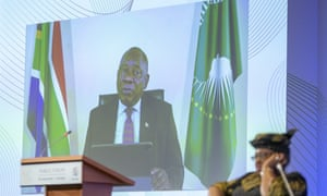 President of South Africa Cyril Ramaphosa is seen on a screen as he delivers his speech past Nigeria's Ngozi Okonjo-Iweala (R), director general of the World Trade Organization (WTO).