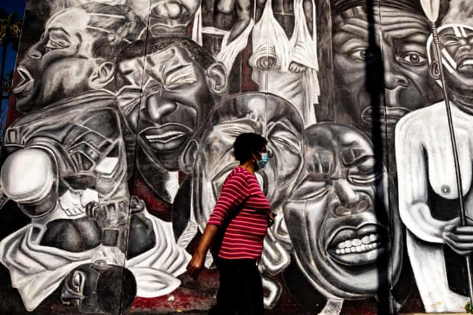 A woman walks by the 1992 mural Freedom Won't Wait by Noni Olabisi in Los Angeles, created after the beating of Rodney King.