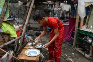 Reymark counts his daily 'catch' of tiny fish outside the makeshift house in Navotas City, Manila, where he lives with his grandparents