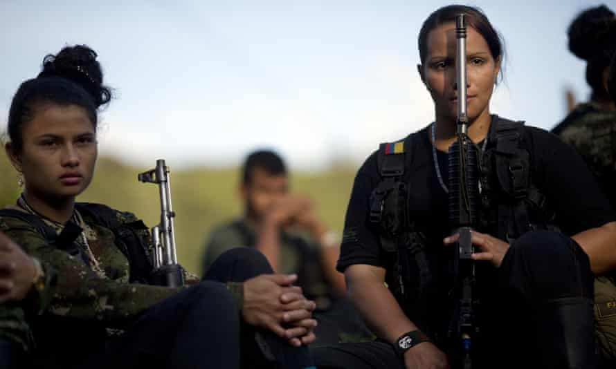 Juliana, 20, left, and Mariana, 24, rebel soldiers for the Farc's 36th Front, listen to a commander speak on the peace negotiations with the Colombian government, in a hidden camp in Antioquia state in January 2016.