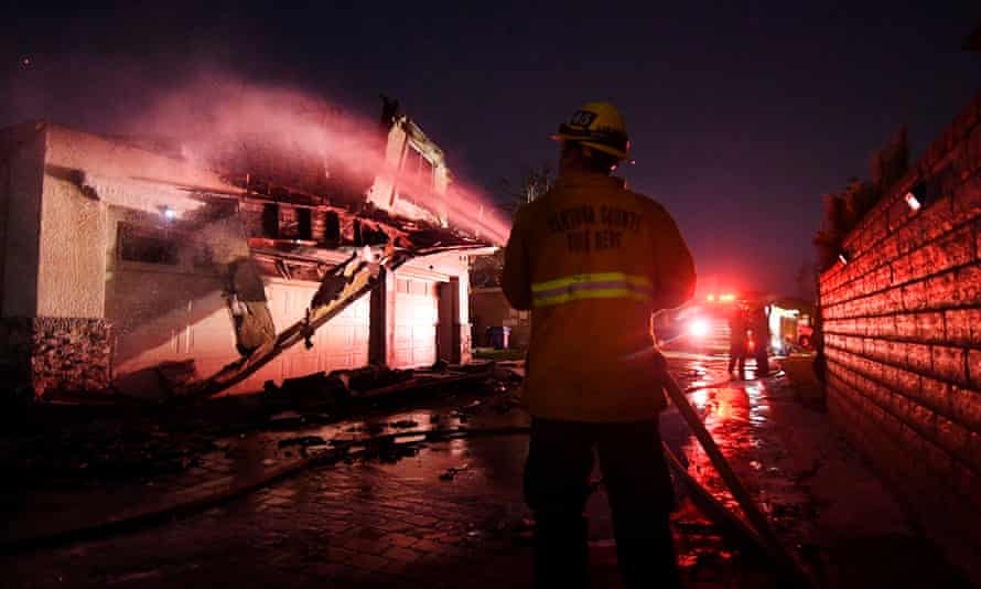 Firefighters hose down a burning house during the Tick fire in Agua Dulce near Santa Clarita, California.
