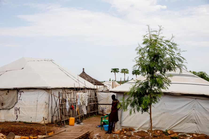 A woman stands near her tent at a camp for internally displaced people in Juba