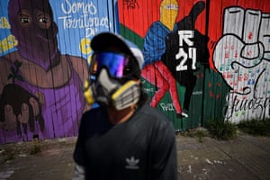 Cali, ColombiaA demonstrator stands next to murals relating to protests against the government of Colombian president, Ivan Duque, in Cali