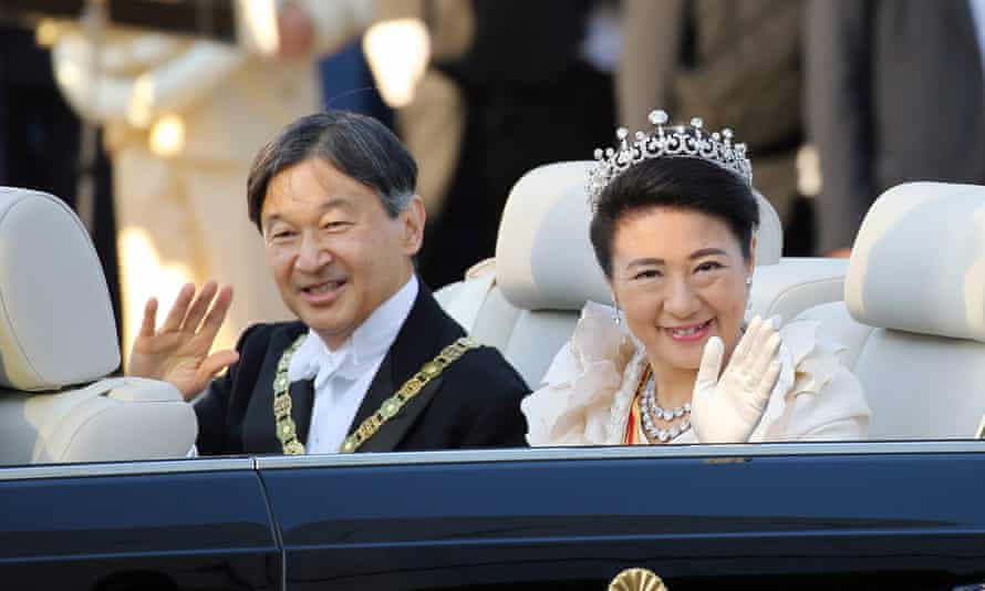 Emperor Naruhito and Empress Masako wave to well-wishers from their car as they parade in Tokyo.