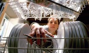 Woman placing saucepan in dishwasher - shot from interior washing up