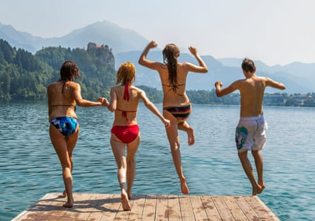 Young people jumping off of a dock into Lake Bled, Slovenia.
