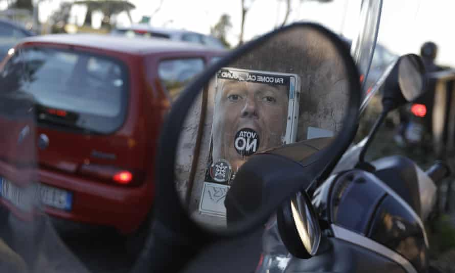 An anti-referendum poster showing Matteo Renzi is reflected in a scooter mirror in Rome.