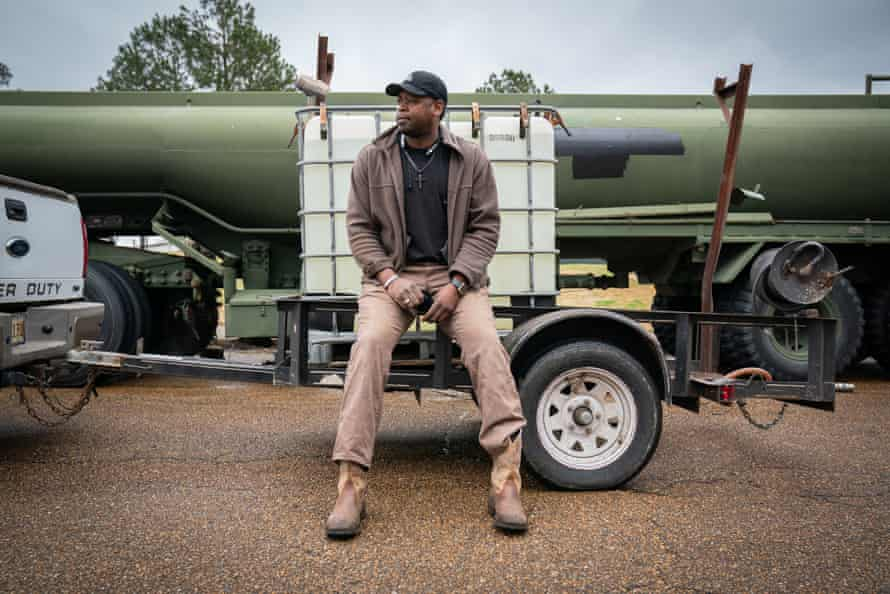 Cedric Weeks poses for a portrait after filling his 900 gallon container at a water distribution site in Jackson, Mississippi on March 2, 2021.