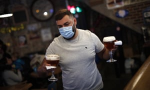A waiter wearing a face mask brings drinks to customers