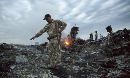 People walk among the debris at the crash site of MH17 in July 2014