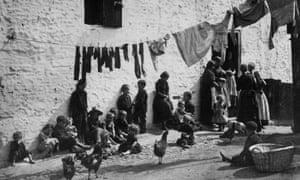 Children sitting under a washing line in a slum area of London, 1889