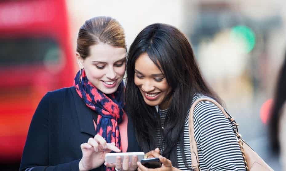 Women using cell phones on city street.