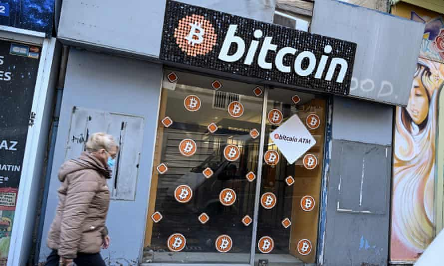 A woman walking past a small shopfront with a big bitcoin sign above the door