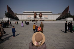 A young family pose for a photograph at Mansu Hill in front of two giant statues of Kim Il-sung and the country's second leader Kim Jong-il