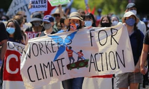 People hold placards during a Workers for Climate Action rally in Sydney on 20 February.