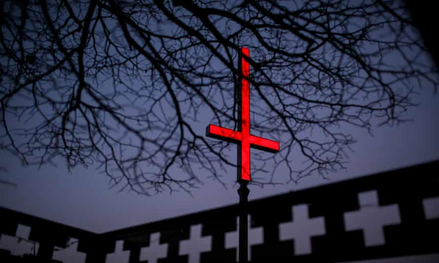 One of the neon red inverted crucifixes on Hobart's waterfront as part of Dark Mofo.