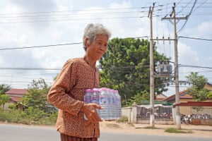 In Cambodia, Em Sro, 73, buys bottled water from a nearby shop to take to her sister, a patient in Koh Thom hospital