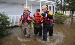 Lumberton North Carolina fire and rescue members help a resident walk through flooded waters in Lumberton, North Carolina on 17 September.