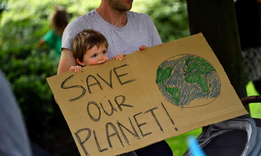 A father and his child hold up a sign as climate activists protest in London, 8 September.