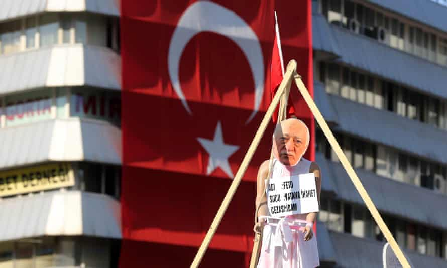 """A picture taken on August 2, 2016 shows  a picture of US-based preacher Fethullah Gulen set up on a dummy at the Kizilay Square in front of a Turkish national flag  in Ankara during a protest against the failed military coup, on August 2, 2016.  Erdogan said on August 2, 2016 last month's attempted coup was a scenario drawn up from outside Turkey, in an allusion to possible foreign involvement in the plot. Erdogan, who blames the plot on the US-based preacher Fethullah Gulen, also described the coup as a """"scenario written from outside"""" in an allusion to foreign involvement.  / AFP PHOTO / ADEM ALTANADEM ALTAN/AFP/Getty Images"""