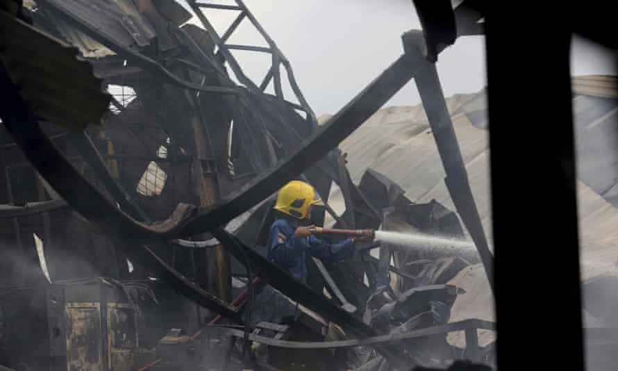 A firefighter sprays water on to the site of an explosion at a firecracker factory in Tangerang