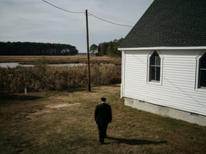 Douglas walks to the rear entrance of New Revived United Methodist Church in Taylor's Island, Md. Decades ago, the church sat in front of forest, now visible open water and marsh come right to the back side of the historic church.
