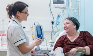 Occupational therapist with woman patient in hospital bed