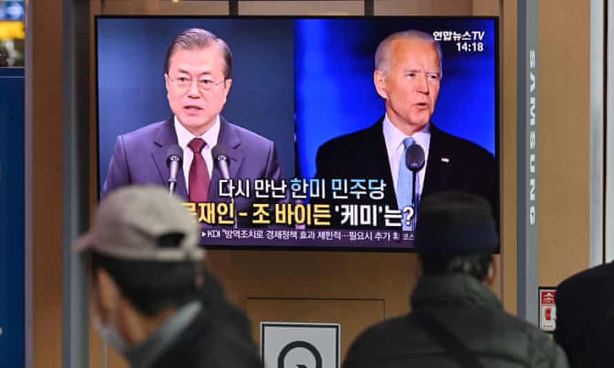 People watch a TV news programme reporting on the US presidential election showing images of Joe Biden and Moon Jae-in