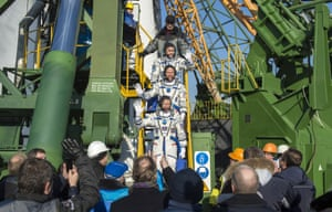 From top, commander Yuri Malenchenko of the Russian Federal Space Agency, flight engineer Tim Kopra of Nasa and flight engineer Tim Peake of the European Space Agency wave farewell before boarding