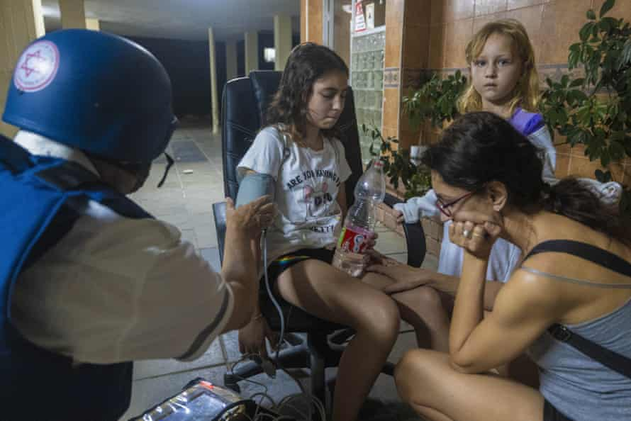 An Israeli paramedic checks the blood pressure of a young girl at residential building after it was hit by a rocket fired from Gaza Strip, in Ashkelon, southern Israel