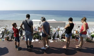 People look at flowers and messages placed along the beach of the Promenade des Anglais in Nice.