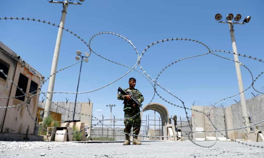 A soldier alone standing guard, framed by coils of razor wire and floodlight towers against a blue sky