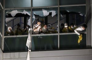Inmates try to breath through broken windows after officers deployed a chemical irritant at the St Louis Justice Centre.