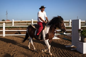 A Vali Ranch worker returns a horse to the stables after a jump show