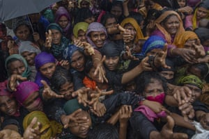 Rohingya Muslim women, who crossed over from Myanmar into Bangladesh, stretch their arms out to collect sanitary products distributed by aid agencies near Balukhali refugee camp, Bangladesh