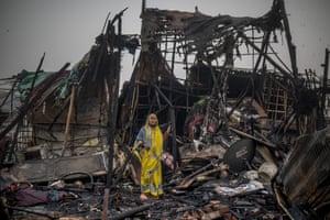 New Delhi, IndiaA woman stands on the debris of a fire in New Delhi.
