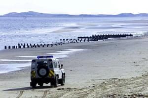 A police Land Rover drives along Brancaster beach in Norfolk