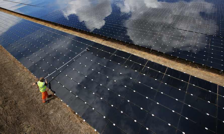 A workman cleans panels at a solar farm