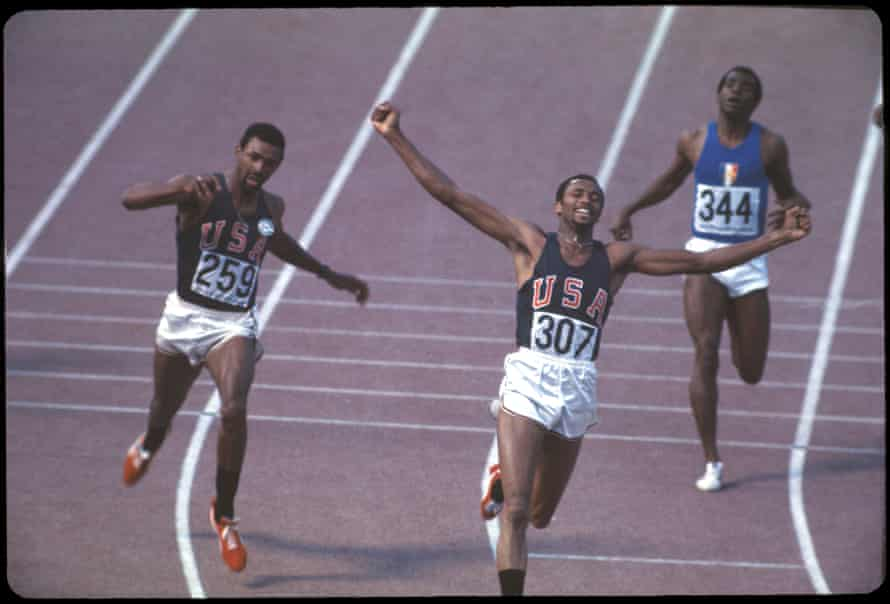 Smith, setting a world record time of 19.83 sec to win the 200m race; Carlos is to his left.