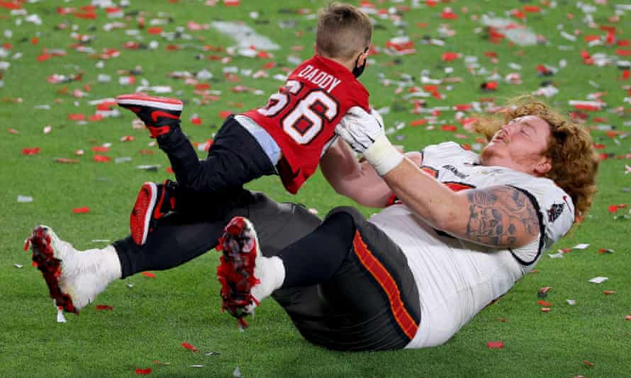 Ryan Jensen celebrates victory with his child after the Bucs' title win