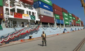 A Pakistan navy soldier stands guard while a loaded Chinese ship prepares to depart from Gwadar.