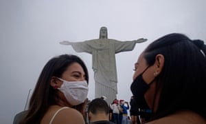 Tourists wearing face masks in front of the Christ the Redeemer statue in Rio