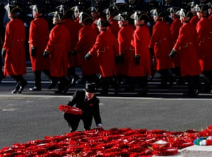 A man lays a wreath as the Chelsea Pensioners parade past during the Remembrance Sunday ceremony at the Cenotaph in London.
