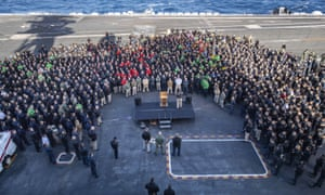 Capt Brett Crozier addresses the crew on the USS Theodore Roosevelt's flight deck in December.
