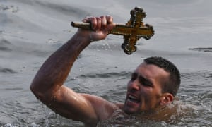 Nikolas Solis holds a wooden crucifix in the Golden Horn in Istanbul, Turkey