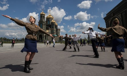 Performers dressed in Soviet era military uniforms dance in front of the cathedral.