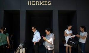 Shoppers queue to enter a luxury store in Tsim Sha Tsui, Hong Kong.